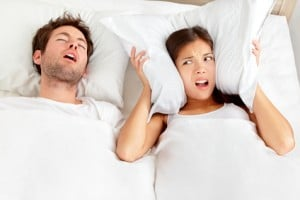 Couple in bed sleeping with man snoring or sleep apnea