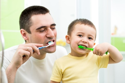 Father and child cleaning teeth